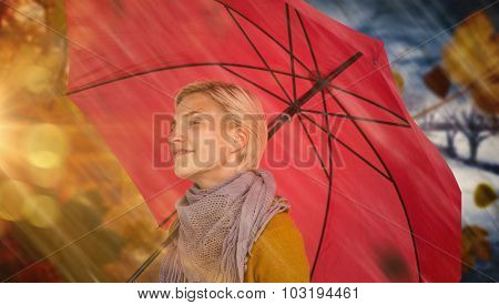 Happy woman keeping dry against autumn turning to winter
