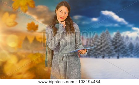 Pensive model wearing winter clothes holding her tablet against autumn changing to winter