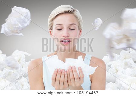 Sick woman holding tissues against grey vignette