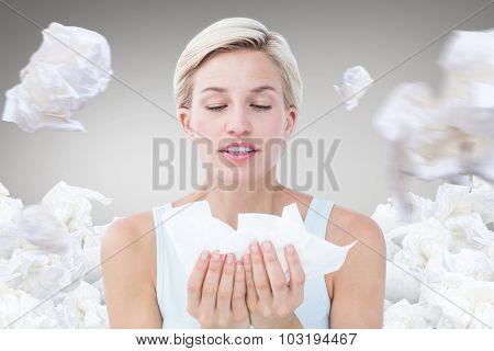 Sick woman holding tissues against grey vignette