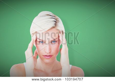 Beautiful blonde suffering from headache looking at camera against green
