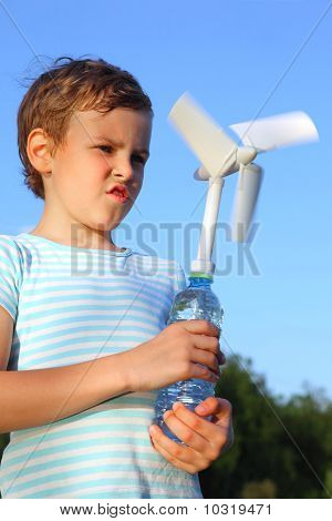 Little Boy Against Sky Plays With Wind-driven Generator