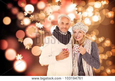 Portrait of happy couple drinking hot coffee against autumnal leaf pattern
