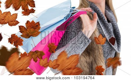 Blonde in winter clothes holding shopping bags against autumn leaves