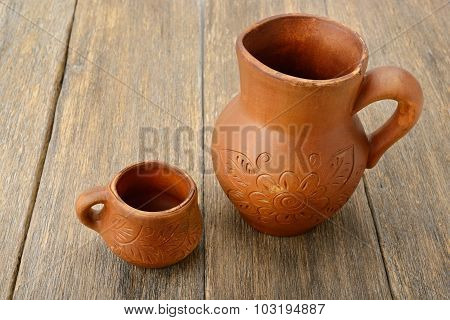 Crock And A Cup On A Wooden Surface