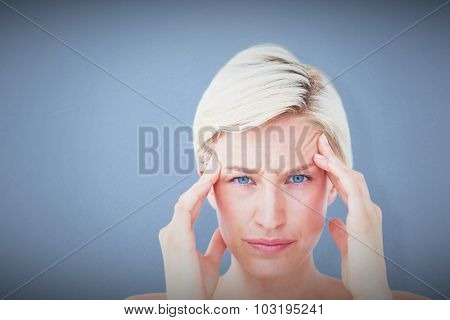 Pretty blonde suffering from headache looking at camera against blue background