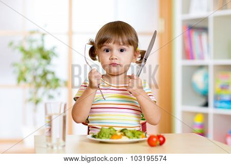 little girl with fork and knife ready to eat