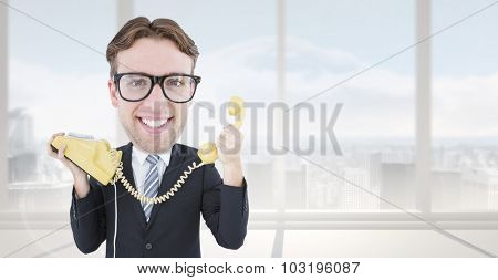 Geeky businessman holding phone against bright white room with windows
