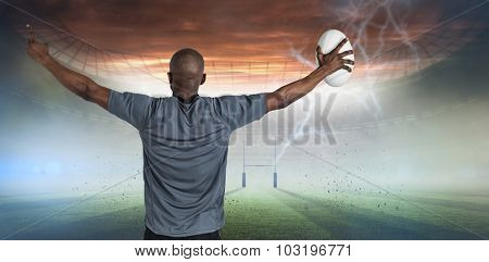 Rear view of sportsman with arms raised holding rugby ball against rugby pitch