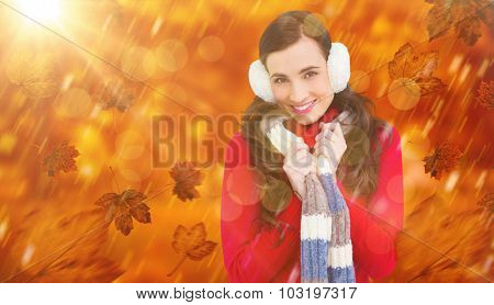 Happy brunette in winter clothes smiling at camera against park