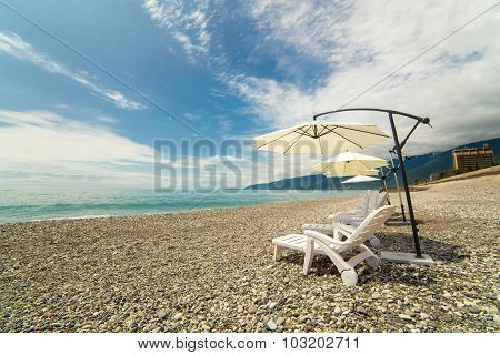 Beach umbrellas and chaise-lounges on the beach