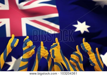 Group of hands giving thumbs up against close-up of australian flag