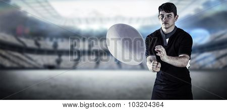Rugby player throwing a rugby ball against rugby stadium