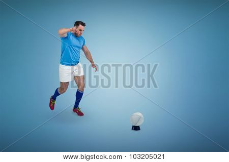 Rugby player ready to kick against blue background