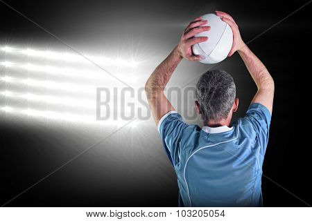 Rugby player about to throw a rugby ball against spotlight