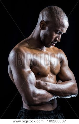 Shirtless athlete standing with arms crossed while eyes closed against black background