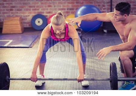 Woman lifting barbell with her trainer in crossfit gym