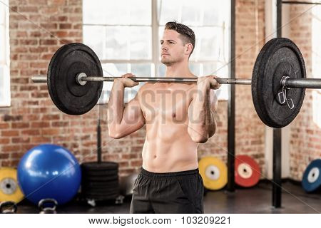 Muscular serious man doing weightlifting in crossfit gym