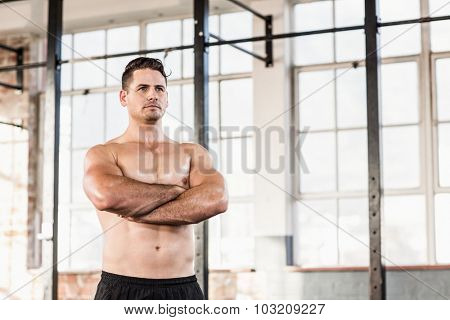 Portrait of shirtless muscular man with arms crossed in crossfit gym