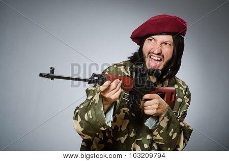 Soldier with handgun against gray
