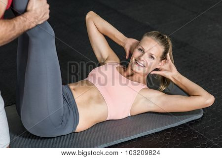 Trainer helping her client stretch legs in crossfit gym