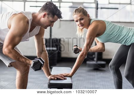 Side view of a couple exercising with dumbbells in gym