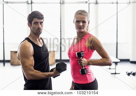Side view of a couple exercising with dumbbells in crossfit gym