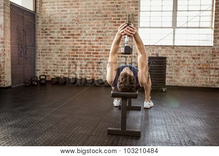Man lifting dumbbell lying on bench at the gym