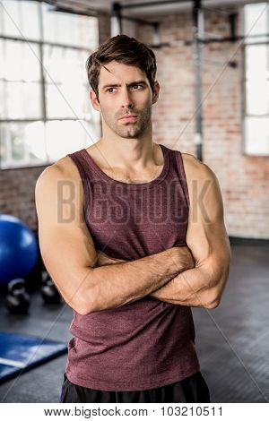 Portrait of a serious man with arms crossed at the gym