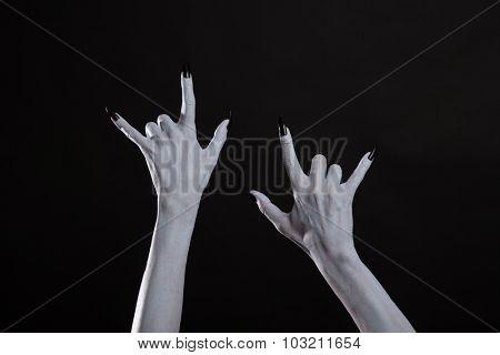 Pale monster hands showing heavy metal symbol, studio shot for Halloween