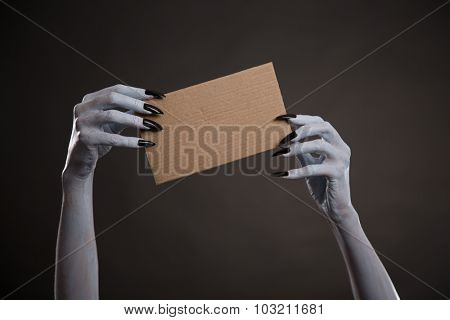 White witch hands with black nails holding blank cardboard, Halloween theme