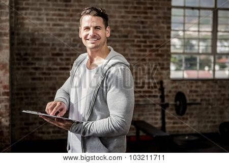 Portrait of muscular man holding clipboard at the gym