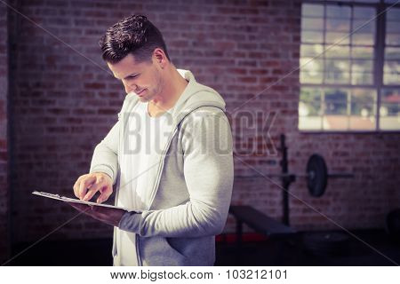 Muscular man holding clipboard at the gym