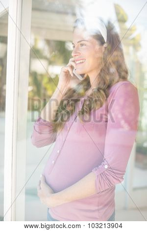 Happy pregnant woman talking on smartphone while looking though window