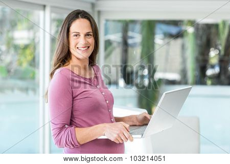 Portrait of businesswoman standing with laptop at home office