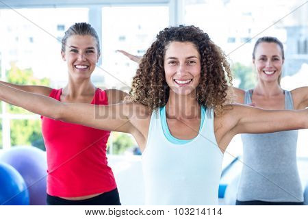 Portrait of women smiling with arms outstretched in fitness studio