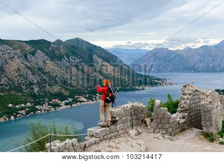 Girl Tourist Photographs The Bay Of Kotor From The Fortress Wall