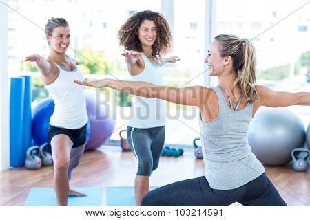 Happy women with arms outstretched in fitness club