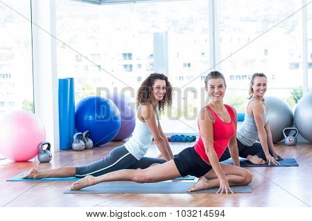 Portrait of women smiling while doing pigeon pose in fitness studio
