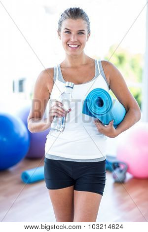 Portrait of smiling woman holding water bottle and yoga mat in fitness studio