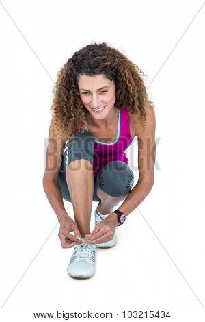 Happy young woman tying shoelace on white background