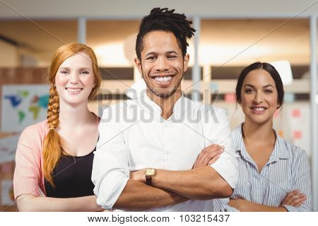 Portrait of confident smiling businessman with female colleagues standing with arms folded in office