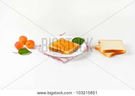white toast bread with apricot jam served on the plate