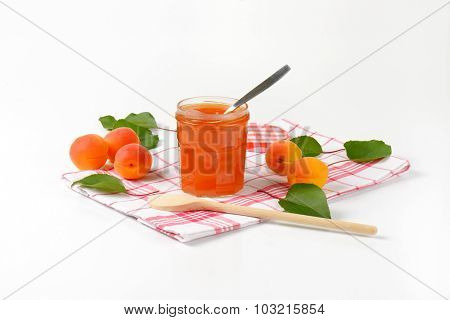 opened jar of apricot marmalade with immersed spoon
