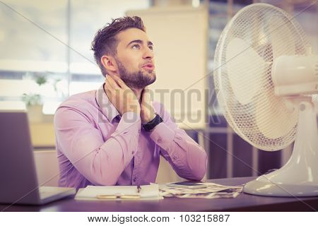 Businessman looking up while sitting at desk with electric fan in office