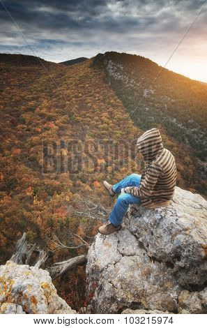 Man in mountain sitting on the cliff. Conceptual scene.