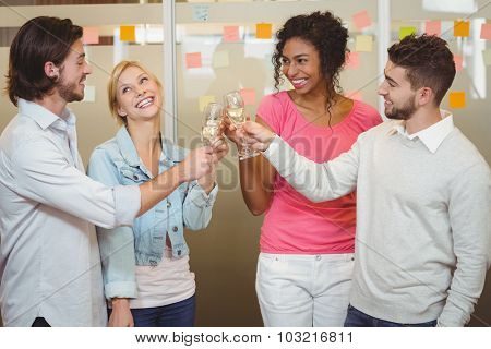 Happy colleagues toasting champagne in party at creative office