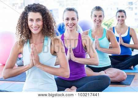 Portrait of women doing easy pose with hands joined in fitness studio