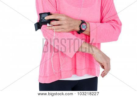 Mid section of woman using mp3 player in armband against white background