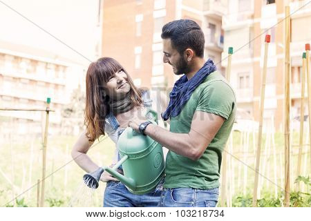 beautiful engaged couple watering plants in the garden